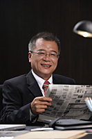 A man smiles at the camera as he reads the newspaper at work - Asia Images Group