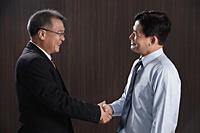 Two men smile and shake hands - Asia Images Group