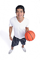 A man holds a basketball and smiles at the camera - Asia Images Group