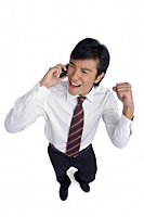A man is excited as he talks on his cellphone - Asia Images Group