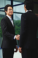 Two men wearing suits shake hands - Asia Images Group