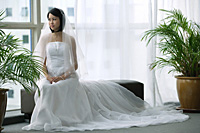 A bride with a white wedding gown sits down - Asia Images Group
