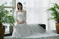 A bride with a white wedding gown sits down and smiles at the camera - Asia Images Group