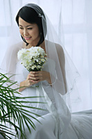A bride smiles as she holds a bouquet of flowers - Asia Images Group
