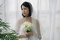 A bride holds a bouquet of flowers - Asia Images Group