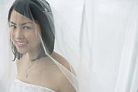 A bride with a veil smiles at the camera - Asia Images Group