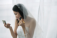 A bride does her makeup in the mirror - Asia Images Group