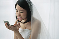 A bride checks her teeth in a mirror - Asia Images Group