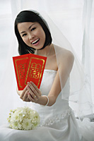 A bride smiles at the camera and holds out two red envelopes - Asia Images Group