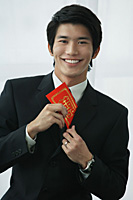 A groom smiles at the camera as he puts a red envelope in his pocket - Asia Images Group