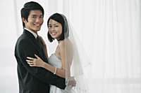 A newlywed couple smile at the camera - Asia Images Group