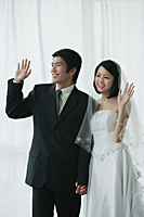 A newlywed couple hold hands and wave - Asia Images Group
