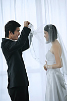 The groom lifts the brides veil to kiss her - Asia Images Group