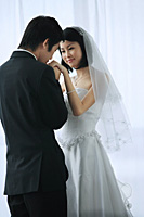 The groom kisses the brides hand - Asia Images Group