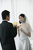 A newlywed couple hold out their champagne glasses for a toast - Asia Images Group