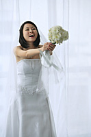 A bride holds out a bouquet of flowers - Asia Images Group