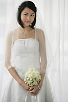 A bride with a bouquet of flowers looks at the camera - Asia Images Group
