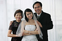 A bride and her family smile at the camera together - Asia Images Group
