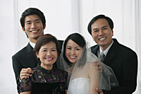 A newlywed couple and their family smile at the camera together - Asia Images Group
