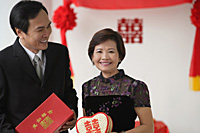 A couple smile as they hold wedding gifts - Asia Images Group