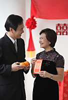 A couple smile as they hold two oranges and a red envelope - Asia Images Group