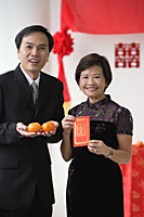 A couple look at the camera as they hold two oranges and a red envelope - Asia Images Group
