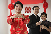 A groom smiles at the camera as he holds out a cup - Asia Images Group
