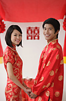 A newlywed couple hold hands and smile at the camera - Asia Images Group
