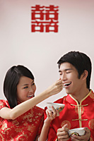 A bride feeds the groom soup from a spoon - Asia Images Group