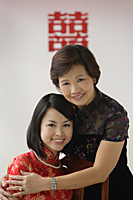 A bride and her mother hug and smile at the camera - Asia Images Group