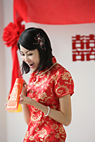 A bride looks excited as she looks inside a red envelope - Asia Images Group
