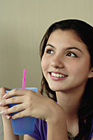 A teenage girl smiles as she has a drink - Asia Images Group