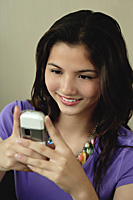 A teenage girl smiles as she uses her cellphone - Asia Images Group