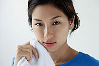 A young woman looks at the camera as she washes her face - Asia Images Group