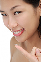 A young woman smiles at the camera a she puts a contact lens in - Asia Images Group