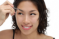 A young woman shapes her eyebrows - Asia Images Group