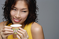 A woman smiles as she has a cup of tea - Asia Images Group