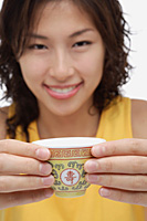 A woman looks at the camera as she holds out a cup of tea - Asia Images Group