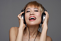 A young woman with headphones on listens to music as she looks at the camera - Asia Images Group
