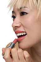 A young woman applies lipstick - Asia Images Group