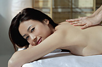 A woman looks at the camera as she has a relaxing massage - Asia Images Group