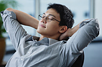 A man relaxes at his desk - Asia Images Group