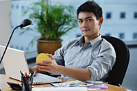 A man looks at the camera as he sits at his desk - Asia Images Group
