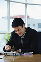 A man plays with a toy car on his desk - Asia Images Group