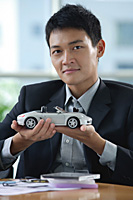 A man looks at the camera as he holds a toy car - Asia Images Group