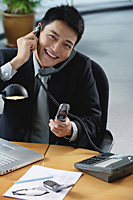 A man smiles at the camera as he sits at his desk which has lots of phones on it - Asia Images Group