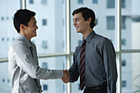 Two male colleagues shake hands - Asia Images Group