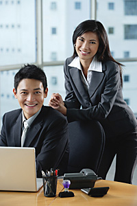 Two work colleagues smile at the camera together - Asia Images Group
