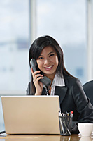 A woman looks at the camera and talks on the phone as she sits at her desk - Asia Images Group