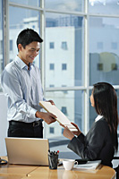 Two colleagues smile at each other as they exchange documents - Asia Images Group
